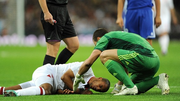 Down and out: Theo Walcott injured following a collision with the keeper